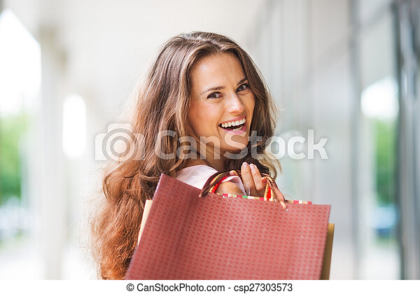 Close-up, over-the-shoulder smiling brown-haired woman shopping - csp27303573