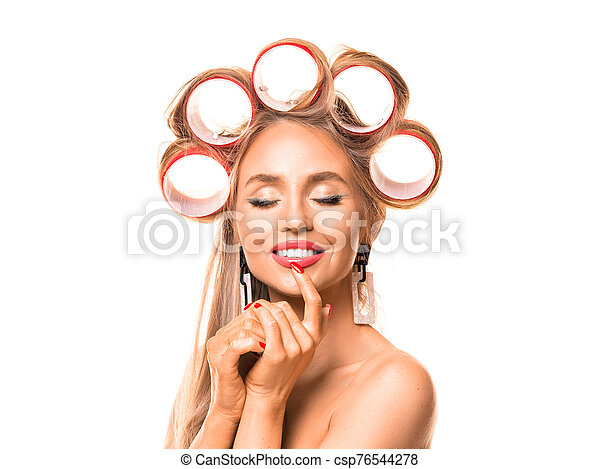 Close up portrait of a beautiful woman with hair rollers on white background. - csp76544278