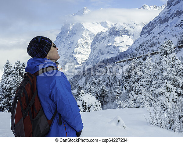 close-up portrait of a tourist looking up at the winter slopes of the mountains, Swiss Alps - csp64227234