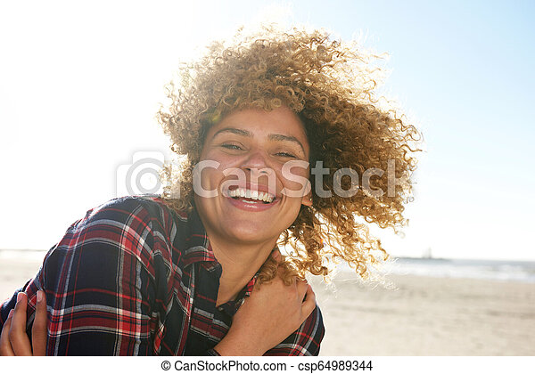 Close up portrait of beautiful african american woman smiling - csp64989344