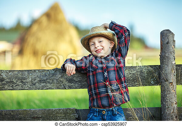 d46bc918c95 Close Up Portrait Of Smiling Little Boy In Hat With Straw In Mouth Leaned  On Wooden Fence