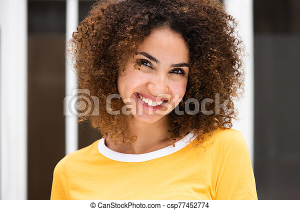Close up portrait of smiling young african american woman with curly hair - csp77452774