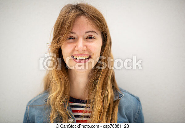 Close up portrait of young woman with long blond hair smiling by white background - csp76881123