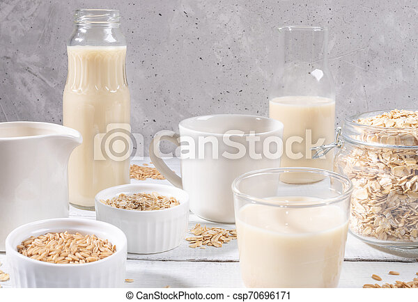 Close-up set of glass containers with oat milk, oat seeds and flakes on white table on concrete background. - csp70696171