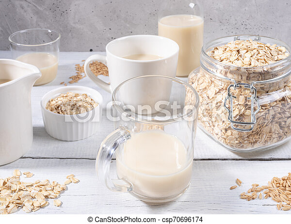 Close-up set of glasses and bottle with oat milk, jar with oat flakes on white wooden table near concrete wall. - csp70696174