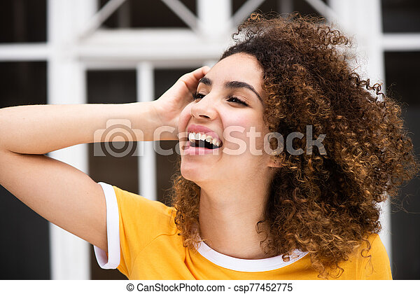 Close up side of smiling young african american woman with hand in curly hair - csp77452775