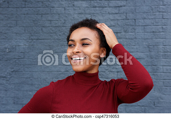 Close up smiling young black woman with hand in hair - csp47316053