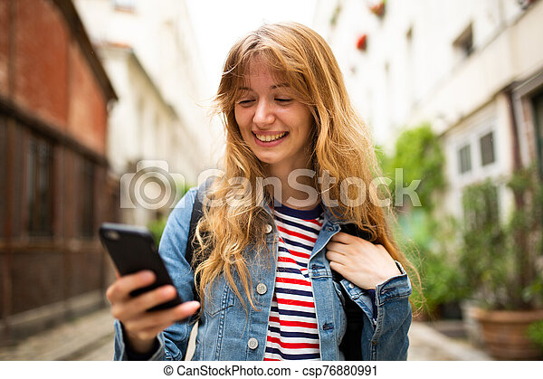 Close up smiling young woman looking at mobile phone in city - csp76880991