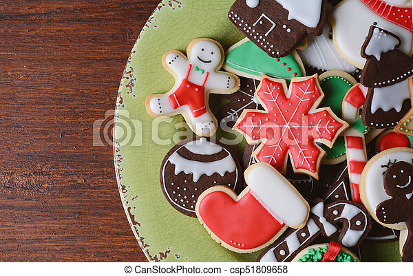 Close up view colorful christmas cookies on wooden table - csp51809658