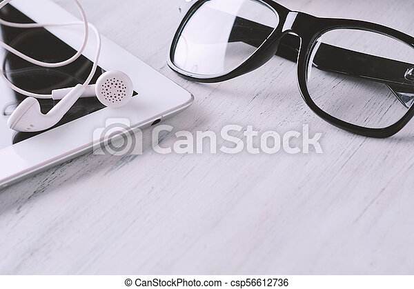 Close up view of glasses, tablet and earphones - csp56612736