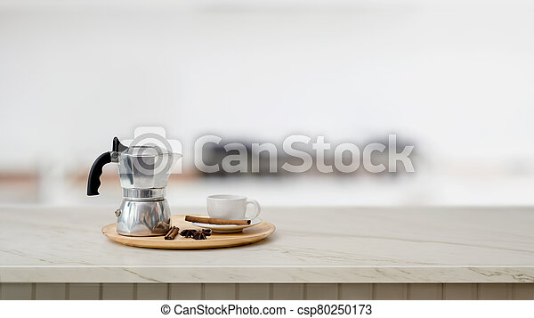 Close up view of mock pot and coffee cup on marble desk with blurred kitchen - csp80250173