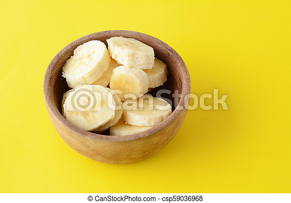 Close up view of wooden bowl with banana slices - csp59036968