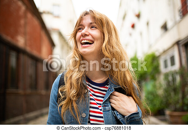 Close up young woman laughing outside in city - csp76881018