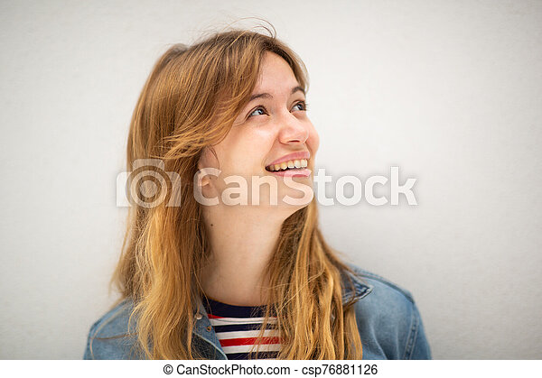 Close up young woman with long blond hair smiling and looking away by white background - csp76881126