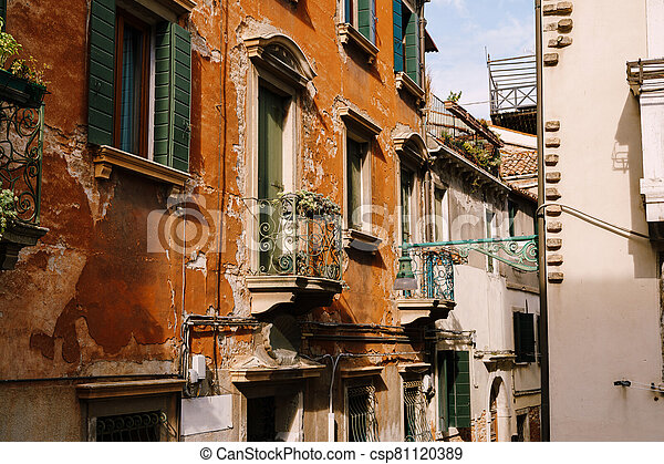 Close-ups of building facades in Venice, Italy. Green wooden door at bottom of brick house. Balcony with a forged fence. An old street lamp on the wall of an apartment building. - csp81120389