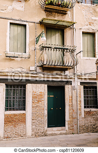 Close-ups of building facades in Venice, Italy. Green wooden door at bottom of brick house. Balcony with a forged fence. An old street lamp on the wall of an apartment building. - csp81120609