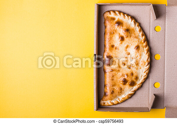 Closed pizza calzone in packing box on yellow background - csp59756493