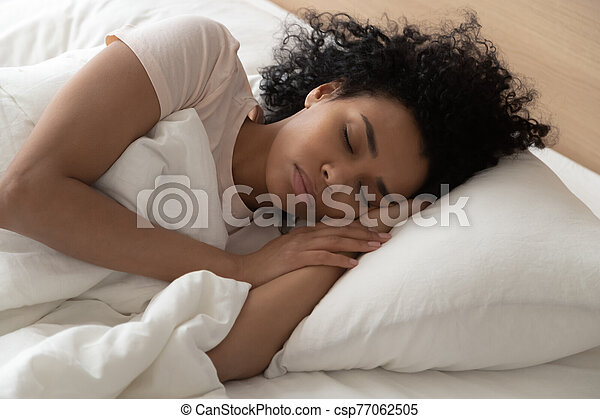 Closeup african woman sleeping in bed at hotel or home - csp77062505