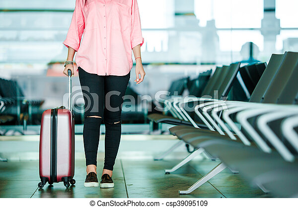 Closeup airplane passenger with passports and boarding pass and pink baggage in an airport lounge. Young woman in international airport walking with her luggage. - csp39095109