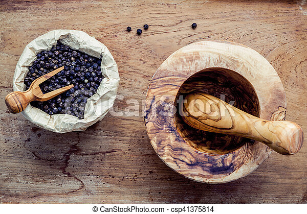Closeup black pepper in wooden bowl with mortar and pestle on shabby teak wood table - csp41375814