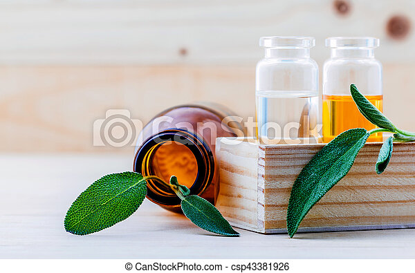 Closeup bottles of sage essential oil for aromatherapy with sage leaves on wooden background. Selective focus shallow depth of field. - csp43381926