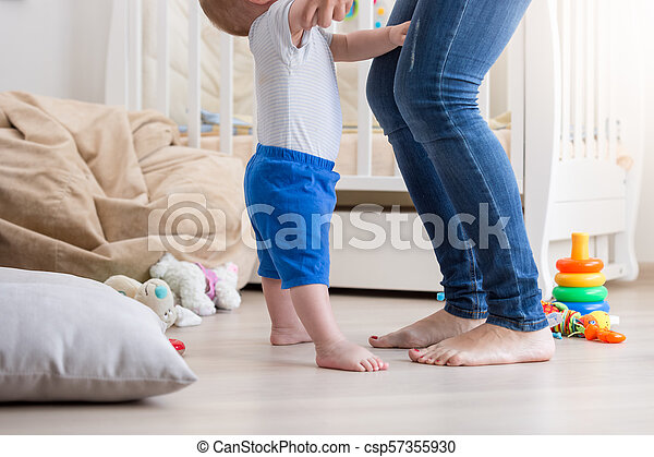 closeup image of baby boy feet standing nest to mothers feet on