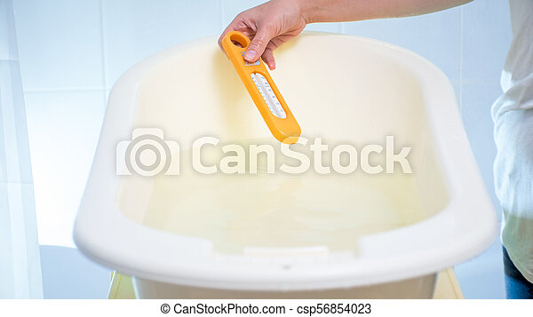 Closeup image of young woman checking water temperature with thermometer in baby bathtub - csp56854023