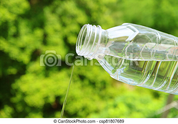 Closeup mineral water flowing from a plastic bottle with blurry green foliage in background - csp81807689