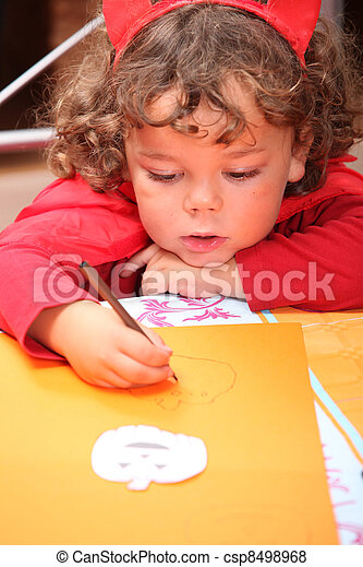 Closeup of a child in a red devil's outfit drawing jack-o-lanterns - csp8498968