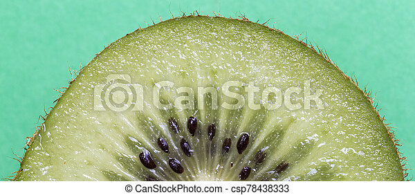 Closeup of a kiwi fruit on a green background - csp78438333