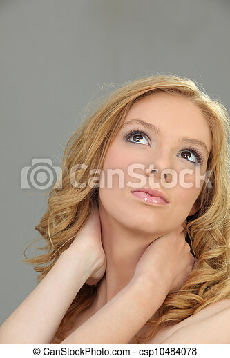 Closeup of a pretty woman holding her neck - csp10484078