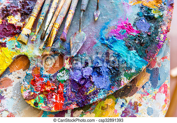 Closeup of art palette with colorful mixed paints and paintbrushed  - csp32891393