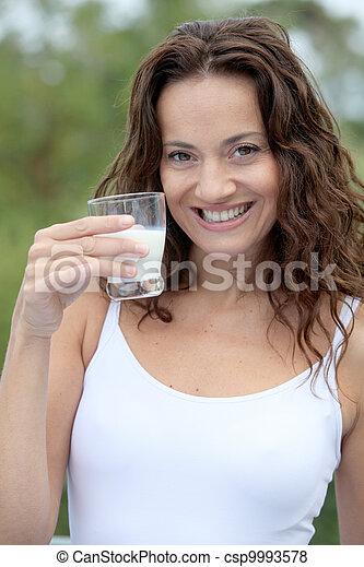 Closeup of beautiful woman drinking milk - csp9993578