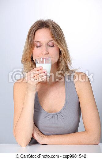 Closeup of beautiful woman drinking milk - csp9981542