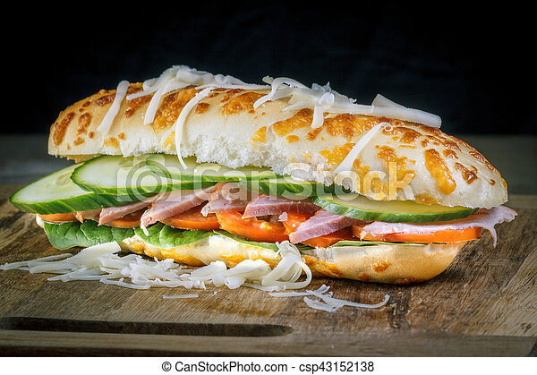 Closeup of Burger on a wooden board with dark background - csp43152138