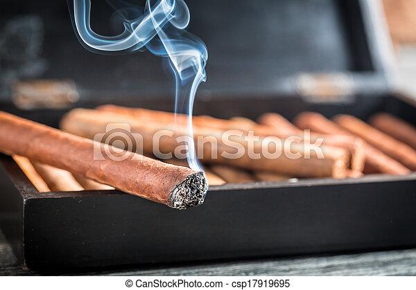 Closeup of burning cigar on wooden humidor - csp17919695