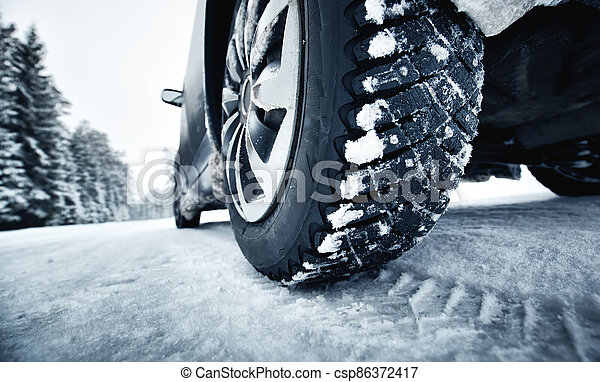 Closeup of car tires in winter on the road - csp86372417
