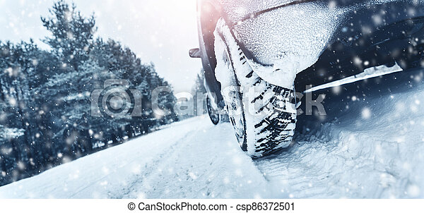 Closeup of car tires in winter on the road - csp86372501