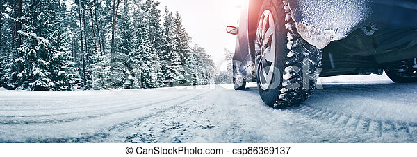 Closeup of car tires in winter on the road - csp86389137