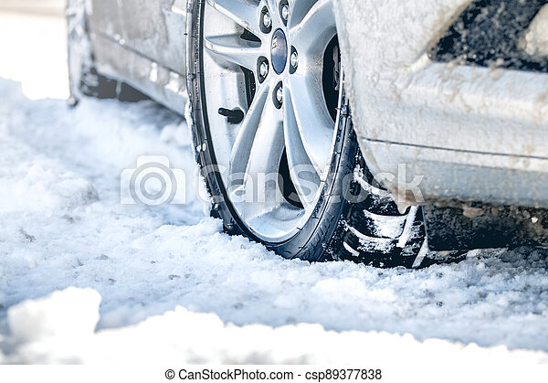Closeup of car tires in winter on the road covered with snow - csp89377838