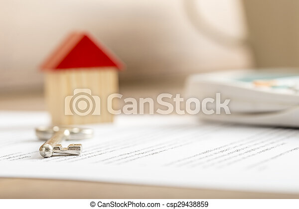 closeup of contract of house sale ready to be signed with wooden toy
