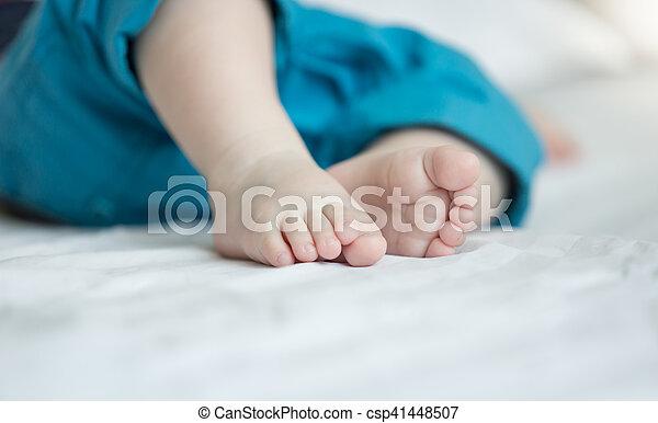 closeup of cute baby boy feet in blue short lying on bed closeup