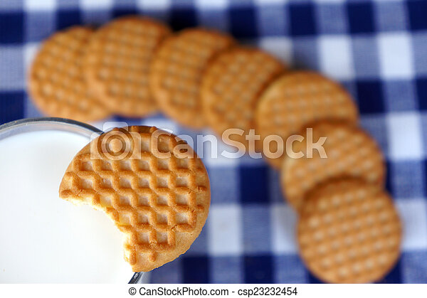 Closeup of dipping a cookie in milk - csp23232454