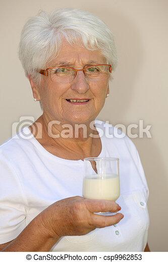 Closeup of elderly woman drinking milk from a glass - csp9962853