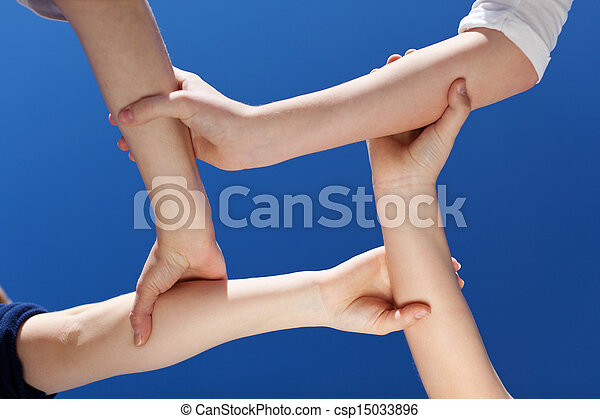 Closeup Of Friends Holding Hands Against Clear Blue Sky - csp15033896