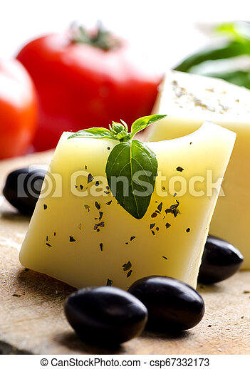 Closeup of goat cheese, olives, fresh tomato, basil and spices on wooden cutting board. - csp67332173