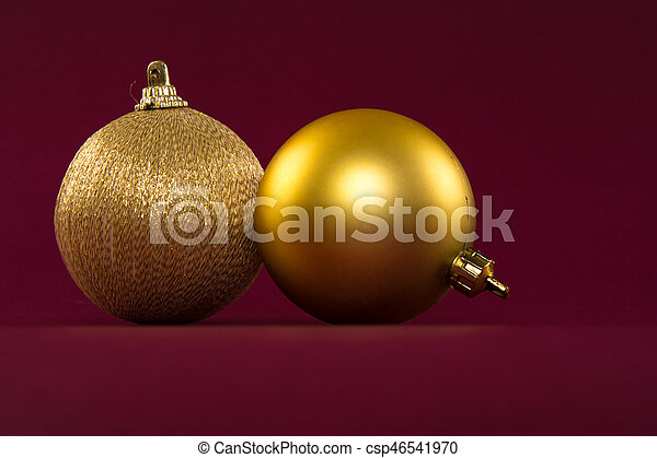 Closeup of golden Christmas balls on a red background - csp46541970
