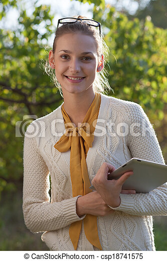 closeup of happy woman in glasses with tablet pc in hands in the park - csp18741575