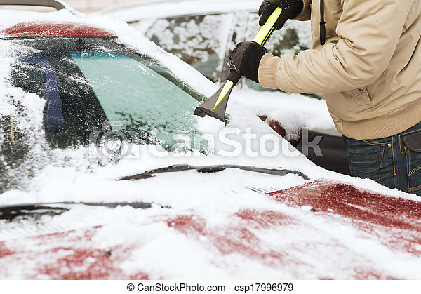 closeup of man scraping ice from car - csp17996979