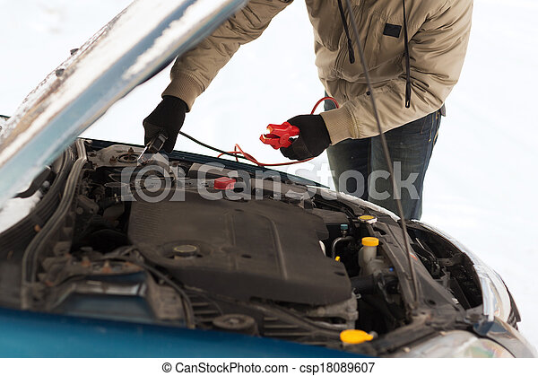 closeup of man under bonnet with starter cables - csp18089607